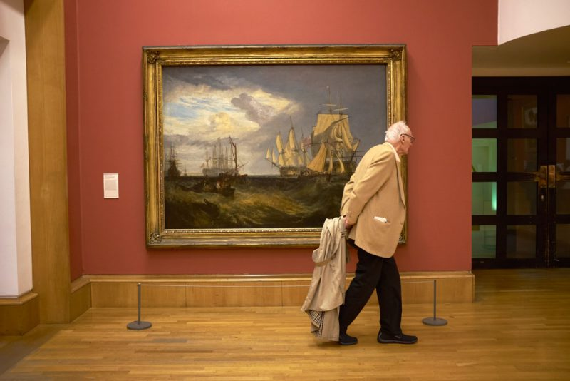 In Tate Britain - a man trailing his raincoat, walking past a painting of ships,