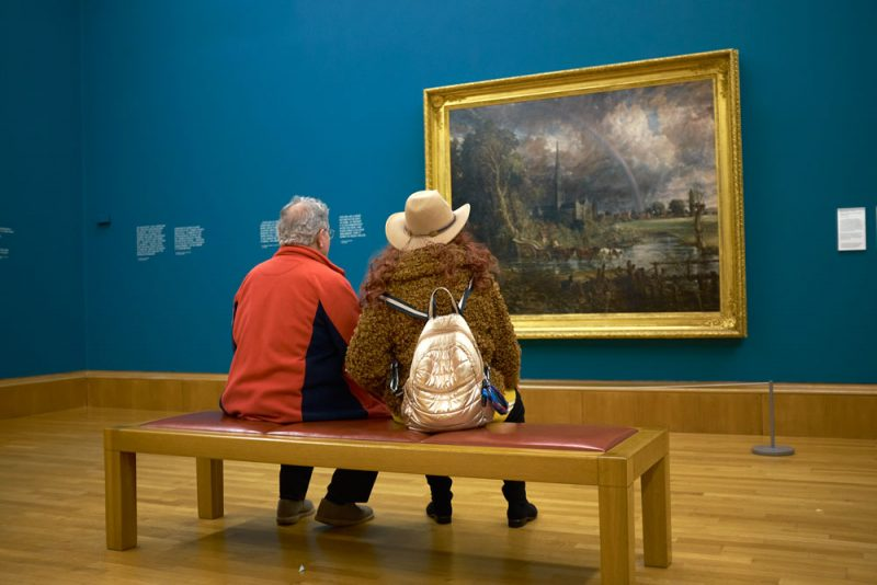 Two people sitting in Tate Britain and looking at John Constable's painting Salisbury Cathedral